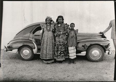 Two ladies and a girl in front of a Peugot 203